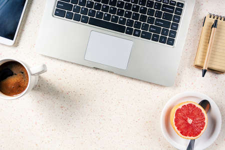 table with smartphone laptop notepad pen cup of coffee plate with grapefruit home office remote working