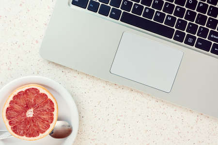 grapefruit on plate and laptop keyboard on the table home office remote working