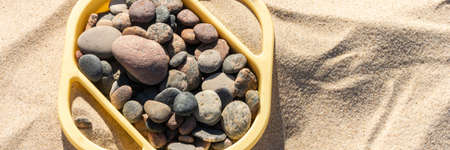 warm stones in box on the yellow sand on the beach horizontal, panorama, panoramic