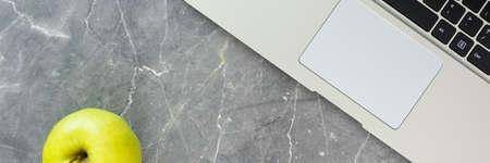 laptop keyboard and green apple on concrete table horizontal, panorama, panoramic