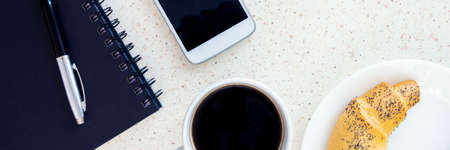 top of table with notebook pen cup of coffee smartphone and plate with twirl horizontal, panorama, panoramic Banque d'images