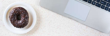 top of desk witk laptop keyboard and plate with donut horizontal panorama