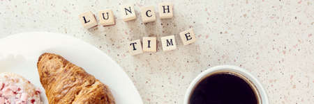 plate of baked sweets cup of coffee and lunch time letters on wooden bloks horizontal, panorama