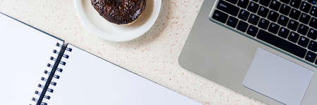 top of desk with notebook pen smartphone plate with donut and laptop keyboard horizontal, panorama