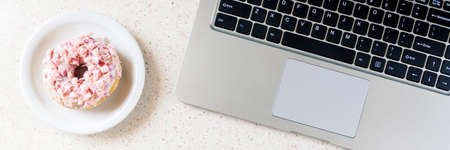 donut on plate laptop and pen on the table horizontal, panorama