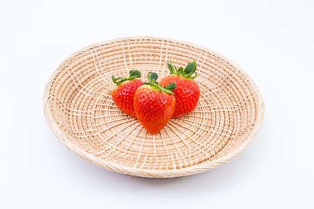 willow fruit basket: fresh sweet ripe strawberries in wicker tray on white background