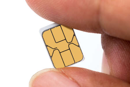 wireles: Hand holding sim card ans sim card tray Stock Photo