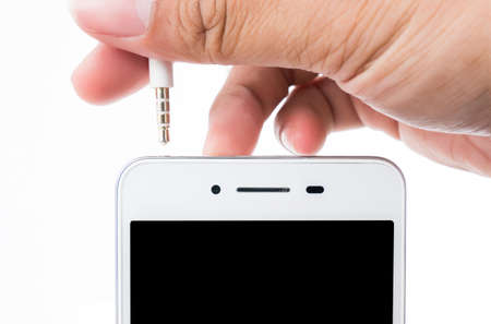 plugging: Hand holding white smart phone and plugging in head phone cable over white background