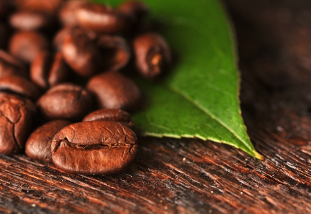 Coffee beans with freen leaf on the wooden board Stock Photo - 16963467