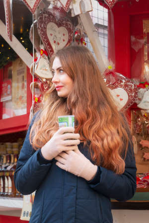 A young girl in gloves with a New Year's drink in her hands against the background of New Year's decorations. Girl with mulled wine in her hands. Editorial