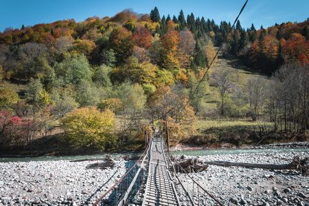 View of a wooden suspension bridge over a river in the mountains in the middle of autumn trees. Autumn high in the mountains, autumn landscape
