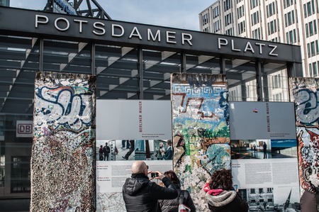 People looking at the rests of the Berlin wall at Potsdamer Platz Berlin in Germany. Editorial