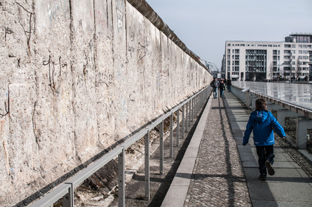 Last remains of the Berlin wall along the ex headquarters of the Gestapo and the SS in Niederkirchnerstrasse 8. the picture people watching wall. Editorial