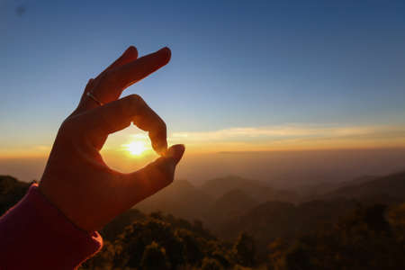 handsign: Ok hand sign silhouette at sunrise. On blue sky background Stock Photo