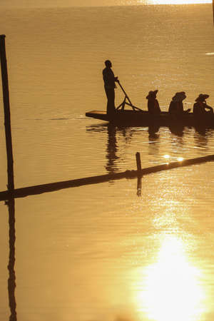 padding: Sillouette of mans padding on lake at sunset