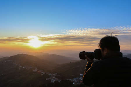 murk: Silhouette of a photographer at sunrise time - photographer taking a landscape picture