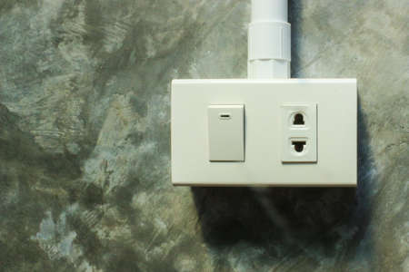 light  house: Close up electric plug and switch on grey wall, background Stock Photo