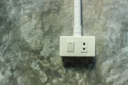 switch plug: Electric plug and switch on grey wall, background