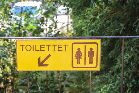 female sex: Public toilet sign with arrow direction on yellow background
