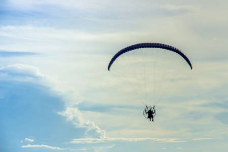 man flying: Silhouette man flying with paramotor in the blue sky background