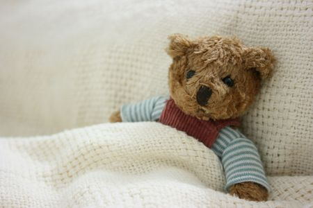Toy bear looked tired in bed