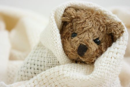Toy bear wrapped in blanket, close-up Stock Photo