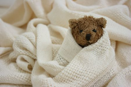 Toy bear is sick, wrapped in blanket