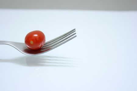 Tomato on fork,side view