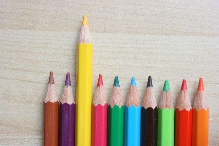 A row of color pencils with an odd yellow color pencil sticking up Stock Photo