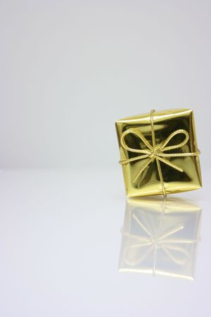 Small present wrapped in gold shiny paper photo