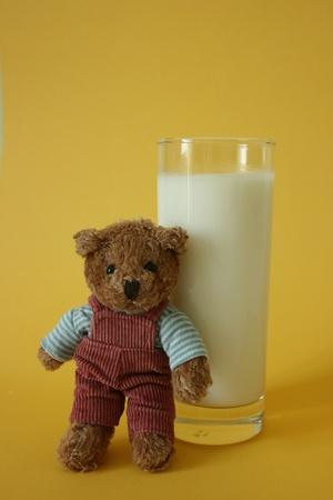 Zabawka miÅ› opierajÄ…c siÄ™ szklankÄ… mleka