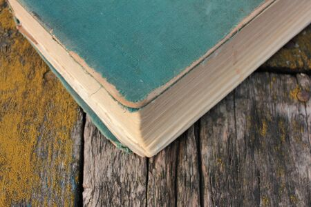 Old shabby book on a rough wooden table covered with moss outdoors. Top view, copy space