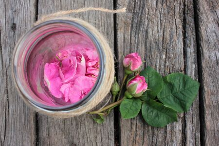 Pink tea rose petals in a glass jar, buds, and flowers on rustic wooden table background.