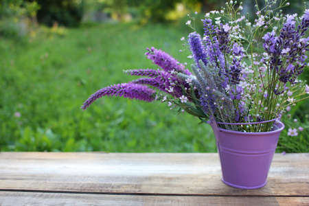 Lavender, veronica, and other purple summer flowers in a decorative bucket on wooden table in the garden. Selective focus. Copy space 免版税图像
