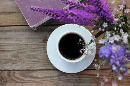 Cup of coffee, book and bunch of purple summer flowers in glass vase on wooden table in the garden. Selective focus. Copy space 免版税图像