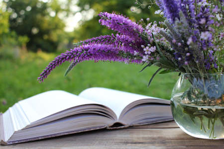 Open book and bunch of purple summer flowers, Lavender, veronica in glass vase on wooden table in the garden. Selective focus. Copy space