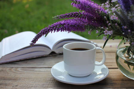 Cup of coffee, open book and bunch of purple summer flowers in glass vase on wooden table in the garden. Selective focus. Copy space 免版税图像