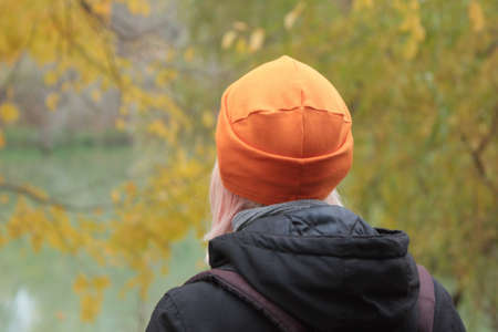 Young woman in bright orange hat on the river and yellow leaves background. Golden autumn landscape