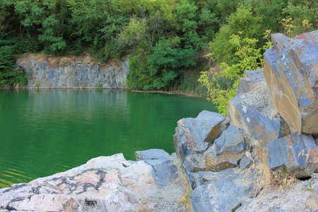 Mountain lake in the summer. Panoramic view on old flooded granite quarry with radon water. Landscape with rock stones, green trees and clean pond