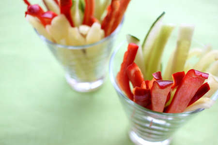 Healthy vegetarian snack for kids. Fresh vegetable sticks from red and green peppers, and cucumber in the glasses. Soft focus