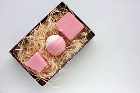 Spa gift basket with set of organic skin care products. Pink candle, bath bomb and handmade rose soap bar in gift box on white background. Christmas, Valentine`s day, Mother`s day, birthday present