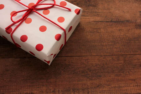 Gift box with red ribbon on wooden background. Top view