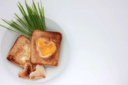 Toast bread with fried egg in a heart shaped hole and greens on plate on white background. Creative Valentine's day or Mothers day breakfast idea