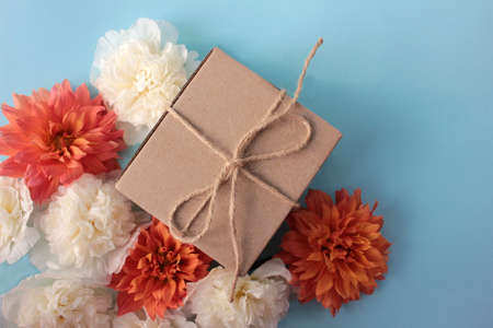Kraft gift box with flowers on colored backdrop. Flat lay composition with present package, orange dahlia and white mallow flowers on blue background.