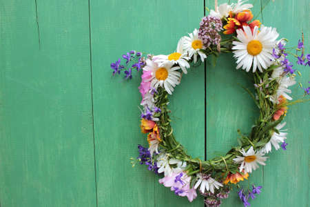 Flower door wreath. Midsummer flower crown on rustic wooden background with copy space. DIY floral wreath. Midsummer night dream decoration