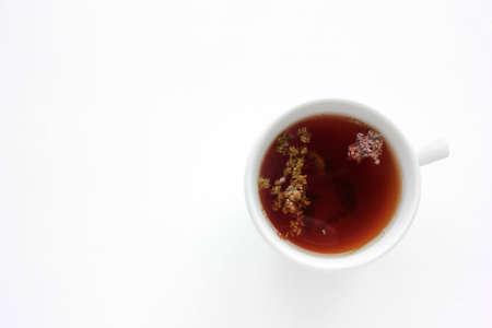 Cup of herbal oregano tea with dry marjoram flowers on white table background with copy space. Top view. Flat lay composition