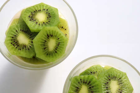 Healthy breakfast yogurt parfait with oatmeal and kiwi in glasses on a white table background. Top view