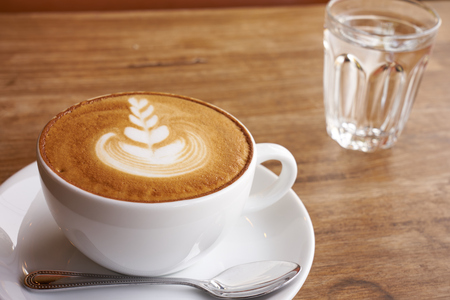 White cup of coffee have latte art foam on top have a glass of water placed on the side. Stock Photo