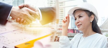 Adult Asian woman architect or engineer wearing helmet standing on surrounded by tall buildings with illustrations of shaking hands and drawing paper with orange lights, business cooperation concept.