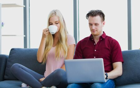 Young couple sitting on sofa, Handsome man searching on laptops to watch multimedia or video streaming online while girlfriend holding a coffee cup within the living room.
